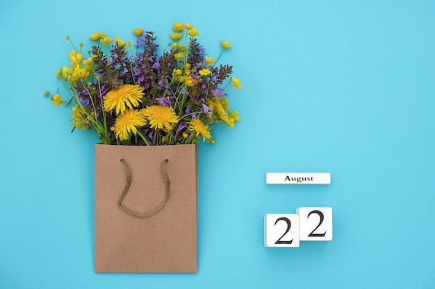 Hölzerner würfelkalender am 22. august und bunte rustikale blumen des feldes im handwerkspaket auf blauem hintergrund