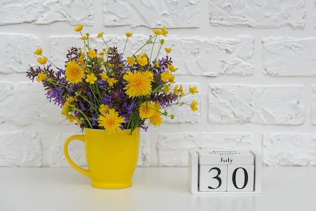 Hölzerner würfelkalender am 30. juli und gelbe schale mit hellen farbigen blumen