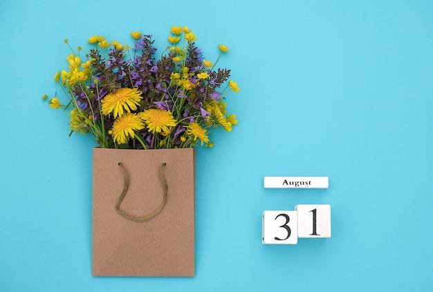 Hölzerner würfelkalender am 31. august und bunte rustikale blumen des feldes