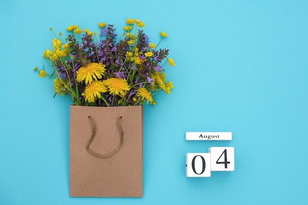 Hölzerner würfelkalender am 4. august und bunte rustikale blumen des feldes im handwerkspaket auf blau.