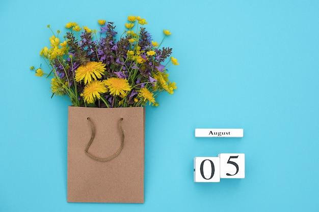 Hölzerner würfelkalender am 5. august und bunte rustikale blumen des feldes im handwerkspaket auf blau