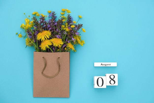 Hölzerner würfelkalender am 8. august und bunte rustikale blumen des feldes im handwerkspaket auf blau