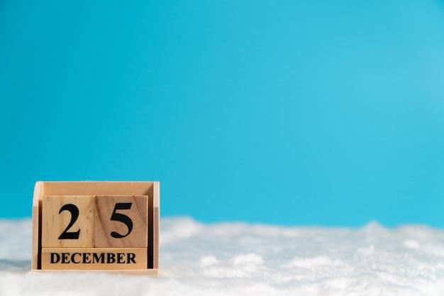 Hölzerner würfelkalender stellte am weihnachtsdatum 25. dezember auf weiße wolle und blaues backgrou ein