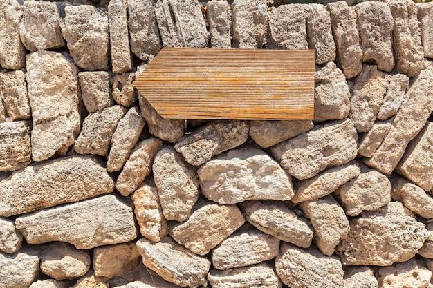 Hölzerner zeiger, der an einer steinmauer hängt. index aus holz.