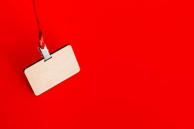 Hölzernes abzeichen mit spitze auf rotem hintergrund
