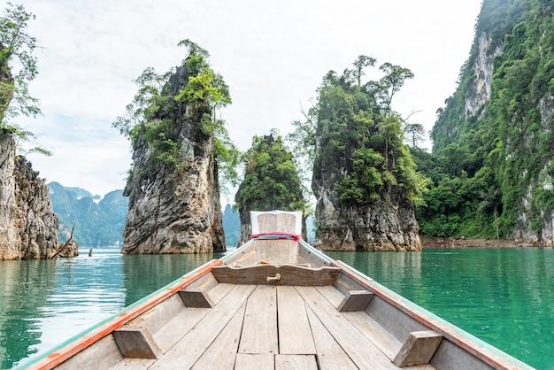 Hölzernes boot des langen schwanzes mit felsenberg und -see in ratchaprapa-verdammung