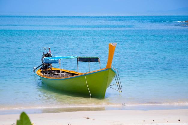 Hölzernes boot mit wind auf der strandreise in südlichem von thailand mit buntem gewebe und holz dieser bootsgebrauch für transport zur insel