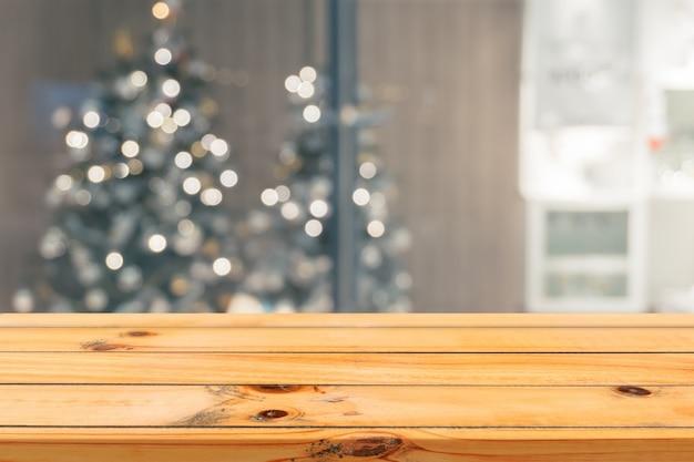 Hölzernes brett leere tischplatte auf unscharfen hintergrund. perspektive braun holz tisch über unschärfe weihnachtsbaum und kamin hintergrund, kann verwendet werden mock up für montage produkte display oder design-layout