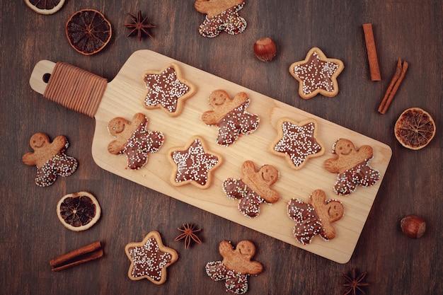Hölzernes brett mit geschmackvollen selbst gemachten weihnachtsplätzchen auf tabelle