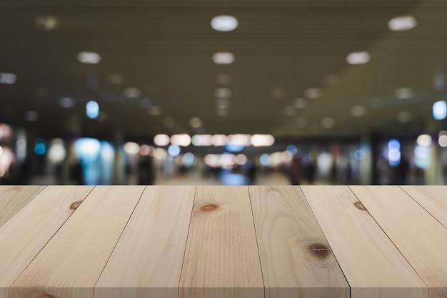 Hölzernes brett über den unscharfen leuten, die in u-bahnstationshintergrund, leere hölzerne tabelle der perspektive über defocus hintergrund gehen