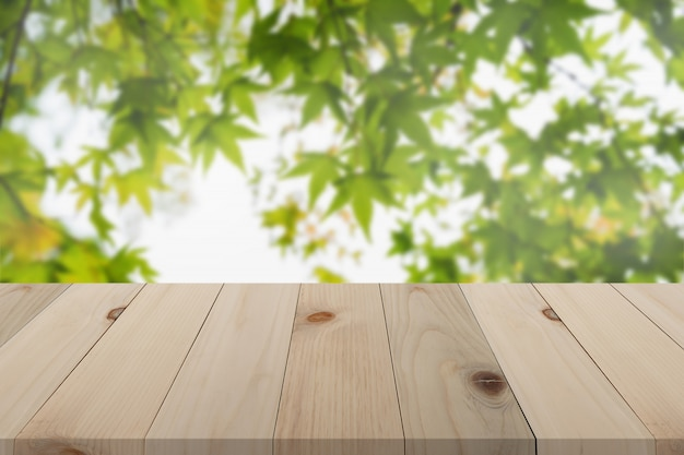 Hölzernes brett über unscharfem ahornblatthintergrund, leere hölzerne tabelle der perspektive über defocus