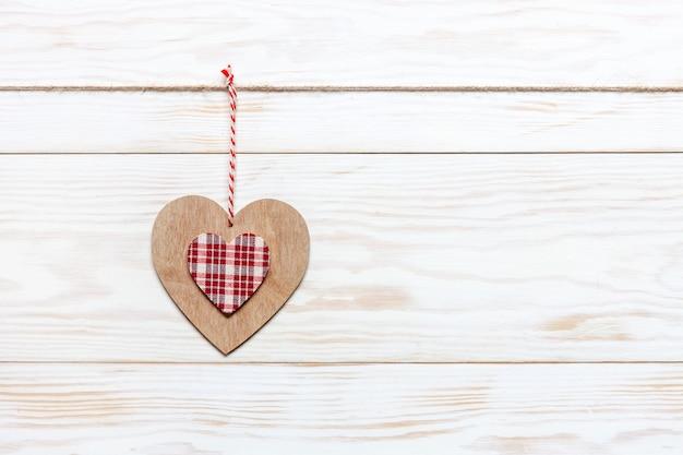 Hölzernes buntes herz auf seil. valentinstag, hochzeit, verlobung und romantische veranstaltungen.