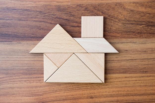 Hölzernes dreieckpuzzlespiel oder -puzzle in der hauptform. traumhaus-konzept.