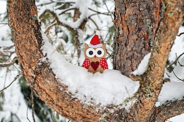 Hölzernes eulenspielzeug im weihnachtsmannkostüm auf schneebedeckter kiefer.