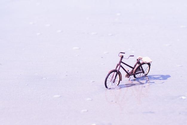 Hölzernes fahrradspielzeughanddicraft am strand auf blauem seeschönem sandnaturhintergrund
