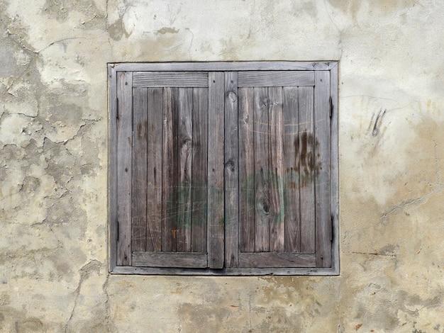 Hölzernes fenster auf altem wandhintergrund