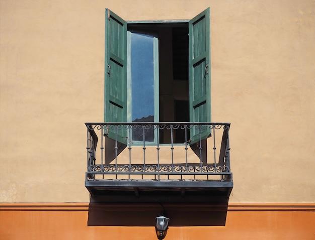 Hölzernes fenster auf orange wand mit balkon