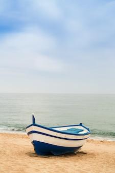 Hölzernes fischerboot auf einem sandigen strand