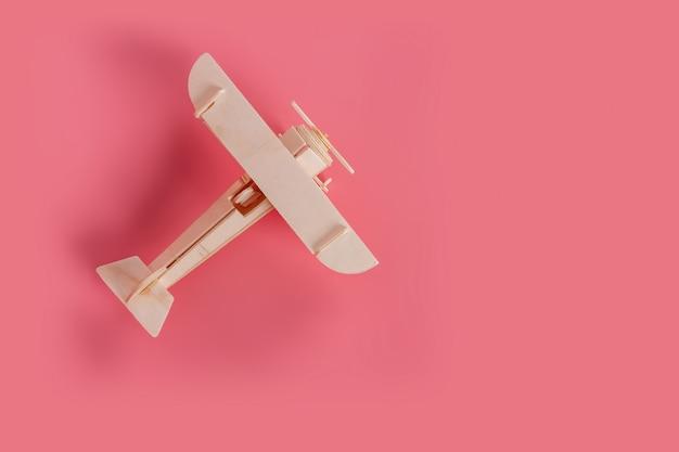 Hölzernes flugzeugspielzeug auf einem pastellrosa hintergrund
