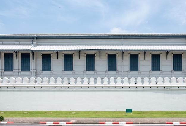 Hölzernes gebäude der architektur mit fenstern auf traditioneller weißer wand