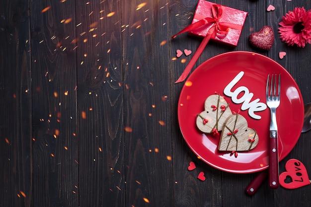 Hölzernes herz auf roter platte für valentinstag mit liebeskonzept für valentinsgrußtag