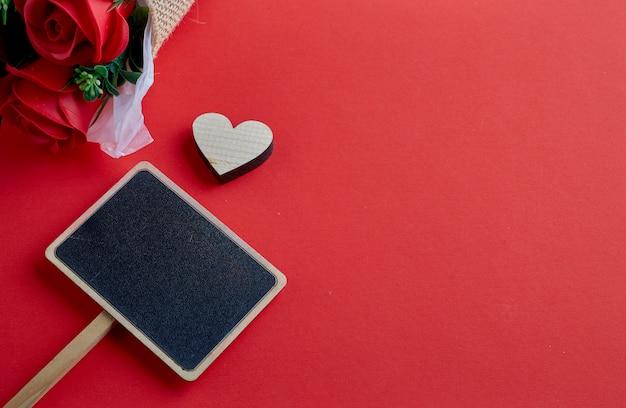 Hölzernes herz des valentinsgrußtages auf rotem hintergrund