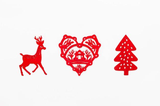 Hölzernes herz mit dem schattenbild des hauses, laufende rotwild, tannenbaum. dekorative rote weihnachtsdekoration.