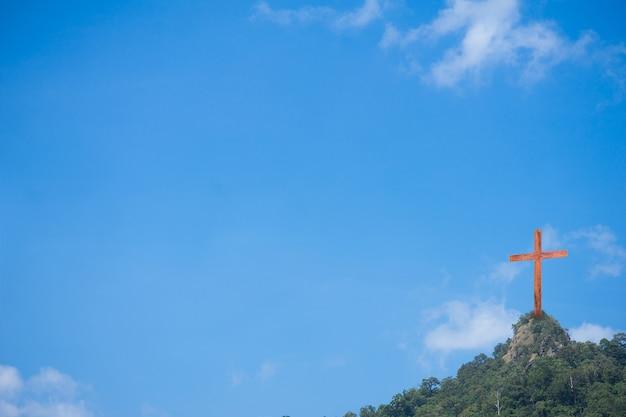 Hölzernes kreuz auf dem hintergrund des berges und des blauen himmels