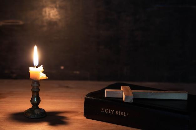 Hölzernes kreuz, das auf eine bibel legt