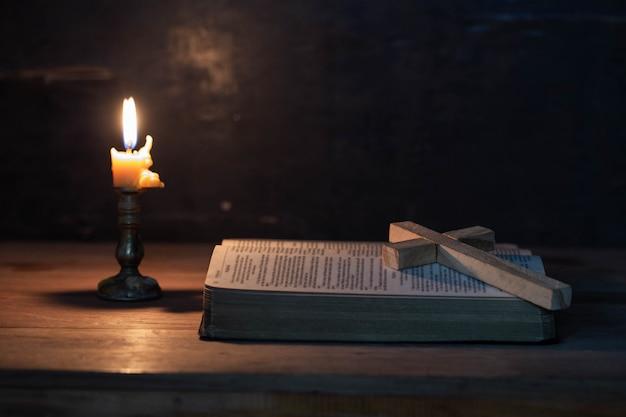 Hölzernes kreuz, das auf eine geöffnete bibel legt