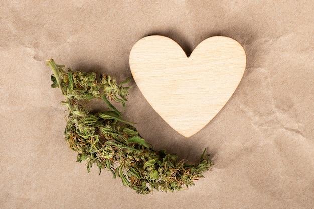 Hölzernes liebessymbolherz und getrocknete cannabisknospe, feiertagsvalentine für marihuanaliebhaber.