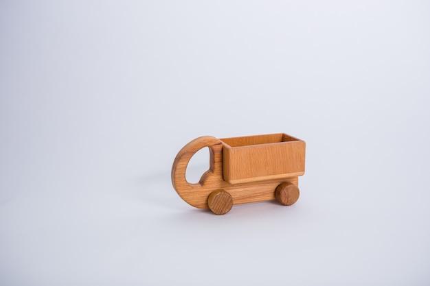 Hölzernes lkw-auto auf einem weißen raum mit kopienraum.