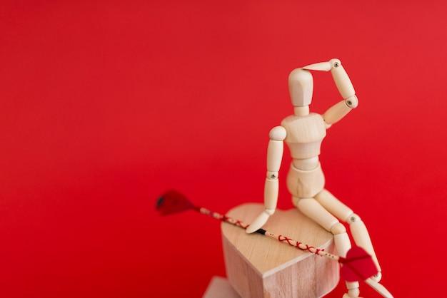 Hölzernes mannequin, das auf herzen mit liebespfeil sitzt
