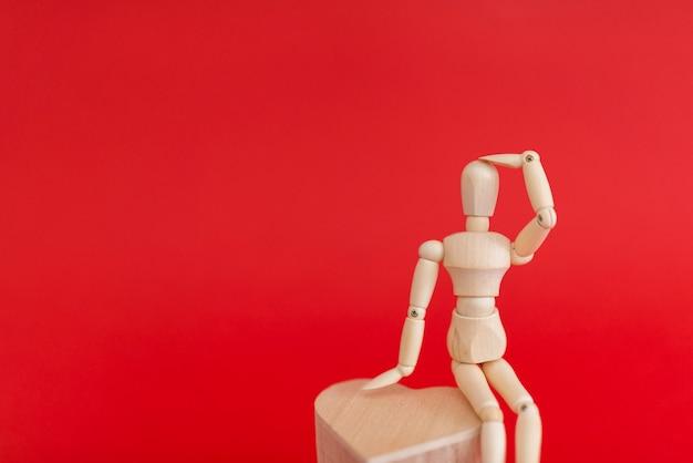 Hölzernes mannequin, das auf hölzernem herzen sitzt