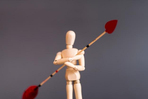 Hölzernes mannequin, das liebespfeil auf grauer tabelle hält