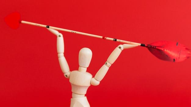 Hölzernes mannequin, das liebespfeil auf rotem hintergrund hält