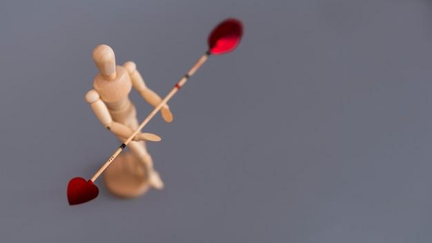 Hölzernes mannequin, das liebespfeil auf tabelle hält