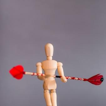 Hölzernes mannequin, das liebespfeil hält