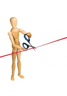 Hölzernes mannequin, das rotes band schneidet