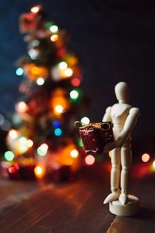 Hölzernes mannequin mit dem geschenk und dem chritsmas-baum