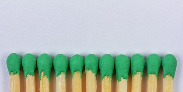 Hölzernes match mit grünem schwefel auf grauem hintergrund mit kopienraumnahaufnahme, draufsicht
