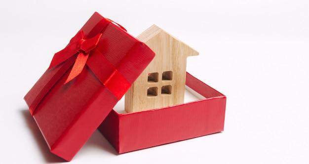 Hölzernes miniaturhaus in einer geschenkbox. wohnen als geschenk. gewinne eine wohnung in der lotterie.