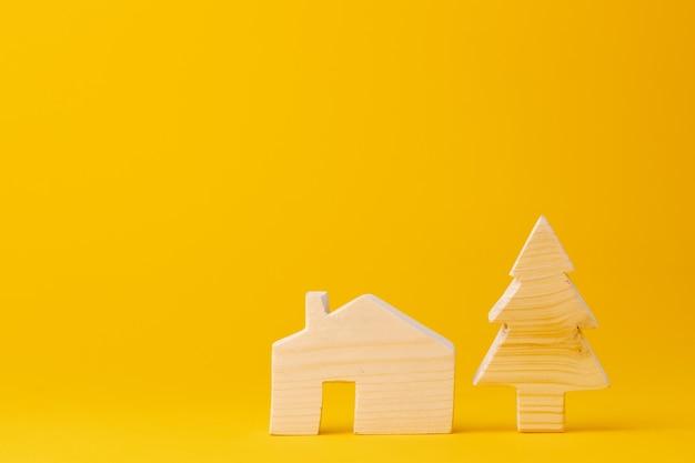 Hölzernes minihausmodell auf gelbem hintergrund
