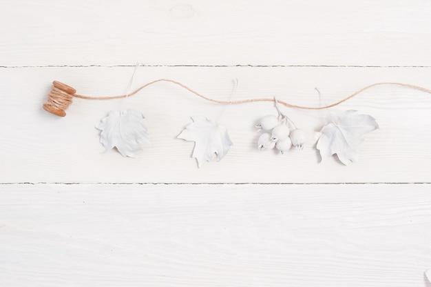 Hölzernes modellherbsthintergrund mit weißem kürbis, beeren, blättern und leinenseil. grußkarte