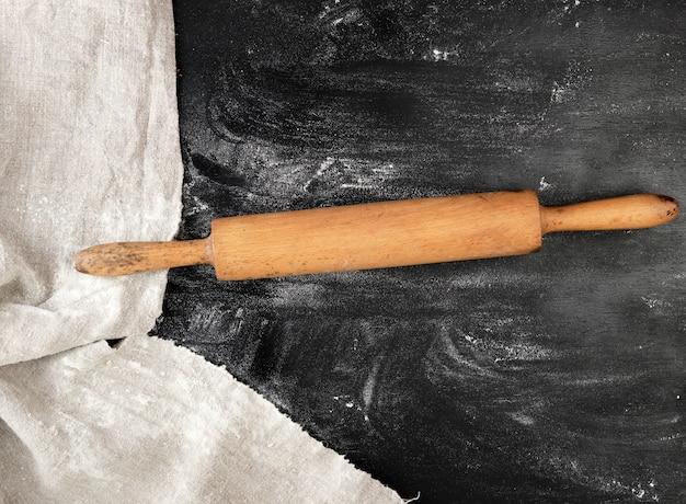 Hölzernes nudelholz auf einem schwarzen hintergrund, weißes weizenmehl