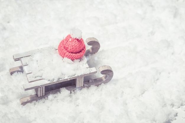 Hölzernes pferdeschlittenspielzeug mit kappe von santa clays auf schnee