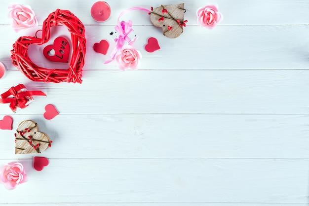 Hölzernes rotes herz auf weißem hölzernem hintergrund. valentinstag hintergrund