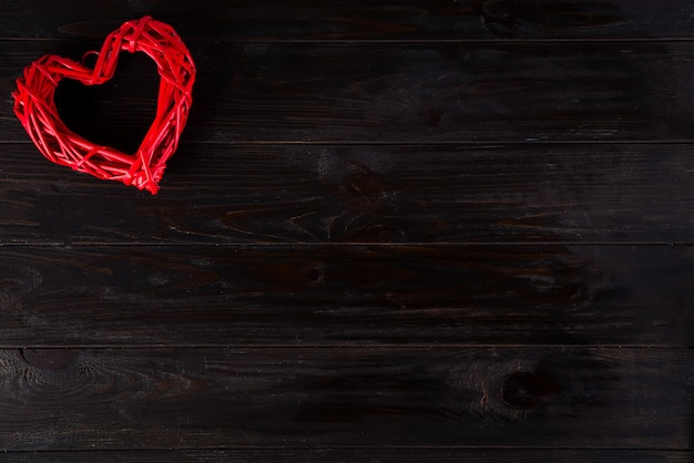 Hölzernes rotes herz, das am dunklen hölzernen hintergrund hängt. valentinstag hintergrund