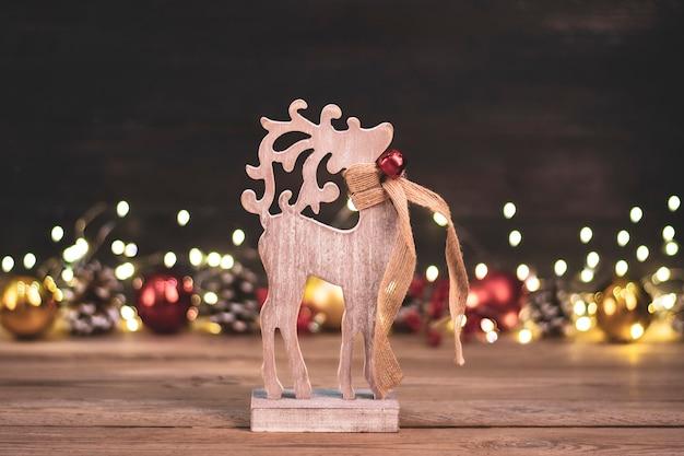 Hölzernes rotwildspielzeug, bokeh, weihnachtsgold, rote kugeln