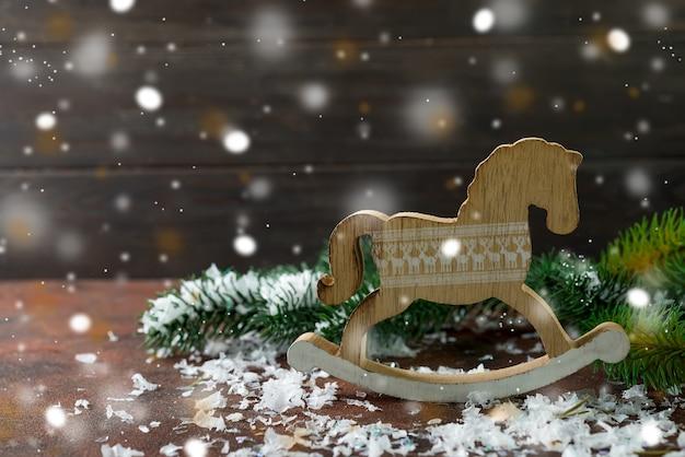 Hölzernes schaukelpferd des spielzeugs als der dekorationen des neuen jahres mit schnee und fer-baum